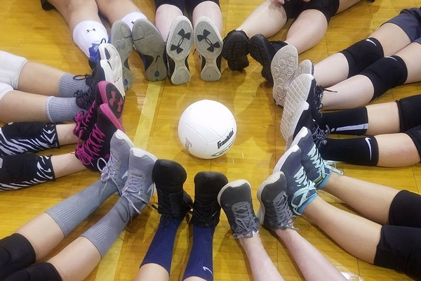 Volleyball team's feet making a circle around a ball
