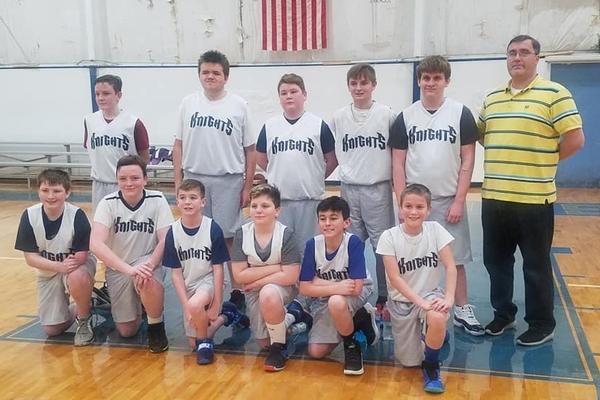 Boys basketball team standing and kneeling for group photo