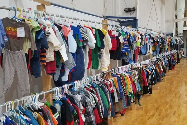 Baby boys clothing hanging on racks in the gym